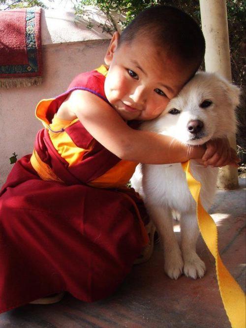 A youngTenzin Phuntsok Rinpoche, reincarnation of Geshe Lama Konchog, hugshis dog, Dorje, Kopan, Nepal. (Photo Unknown)