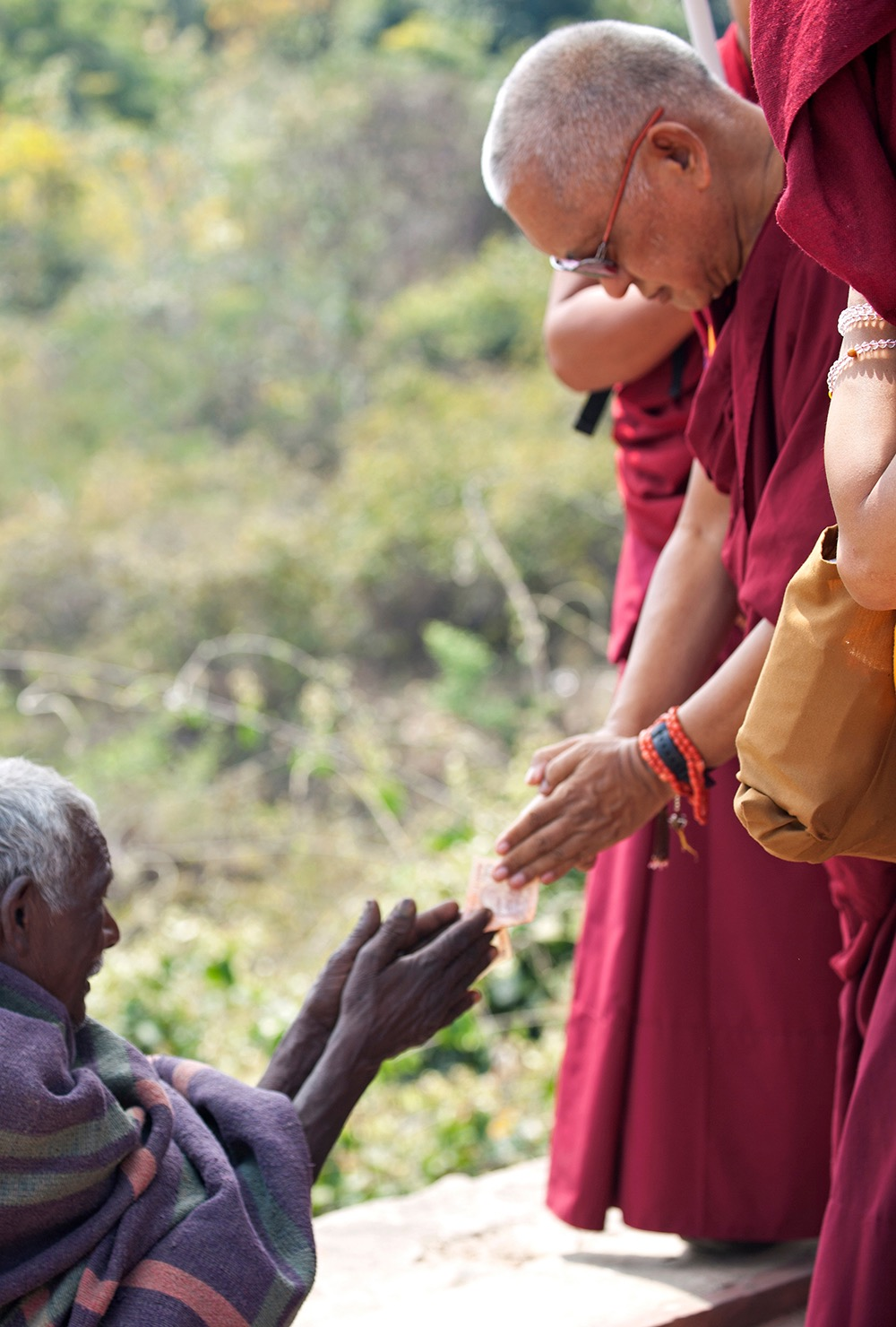 Rinpoche making charity respectfully to a beggar at Vulture'sPeak, India. (Photo Andy Melnic)