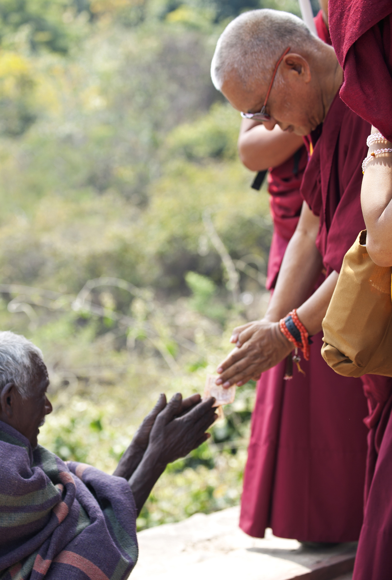 Lama Zopa Rinpoche respectfully offersto a beggar on the way up to Vulture's Peak, Rajghir, March 2014. (Photo Andy Melnic)