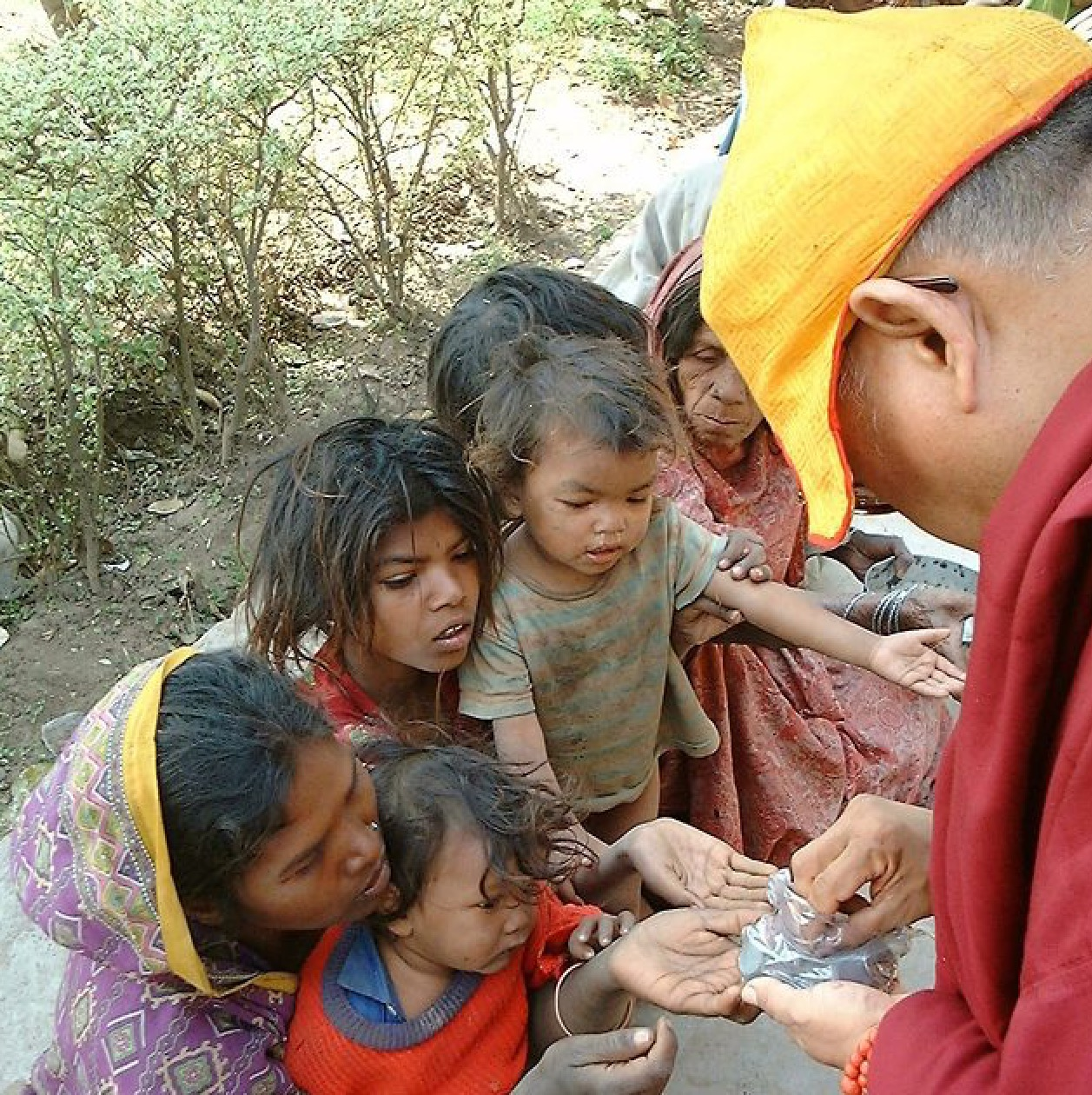 Rinpoche giving to the beggars in India. (PhotoVen Roger Kunsang)