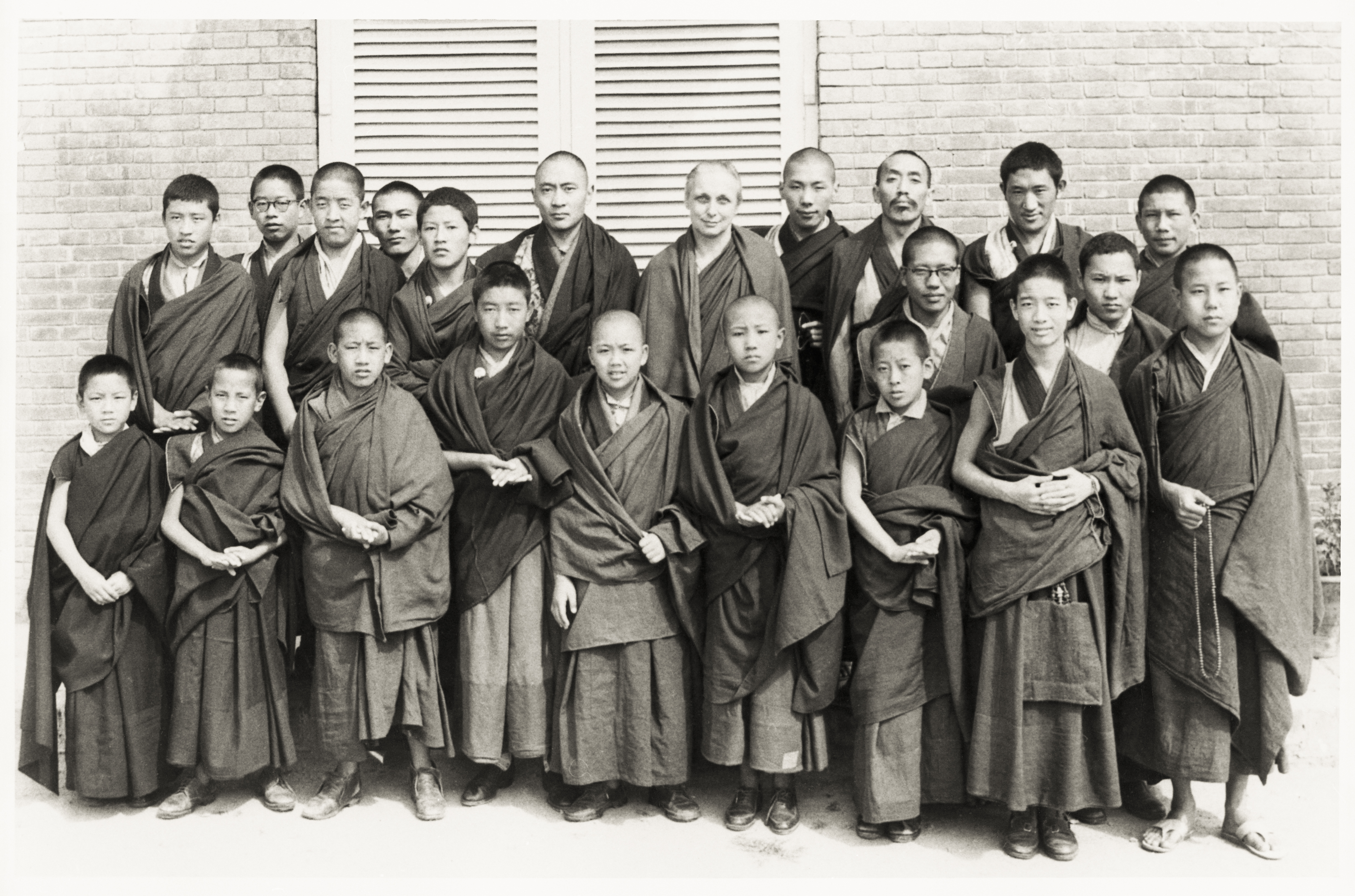 """The Young Lamas School in India with Freda Bedi and Trungpa Rinpoche in the back row and a young Lama Zopa Rinpoche standing to the far left next to Thepo Tulku. Lama Zopa Rinpoche says, """"That is me at school. I was older than Thepo Tulku although my body looks smaller.""""(PhotoShambhala Archives Collection)"""
