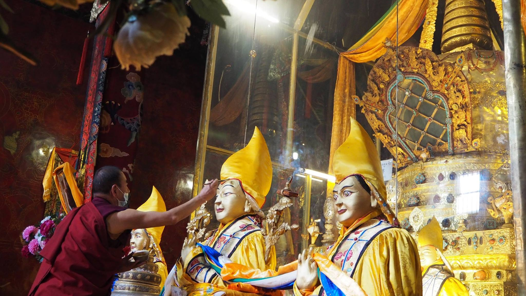 A monk applies gold to the statue of Lama Tsongkhapa in front of the stupa of his relics at Ganden Monastery, Tibet. (Photo Ven Tenzin Tsultrim)