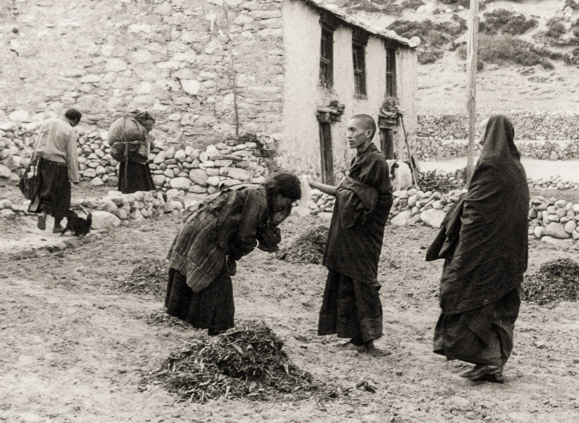 Lama looks on as Rinpoche, the Lawudo Lama, blesses a Sherpa woman on the way to Lawudo, 1969