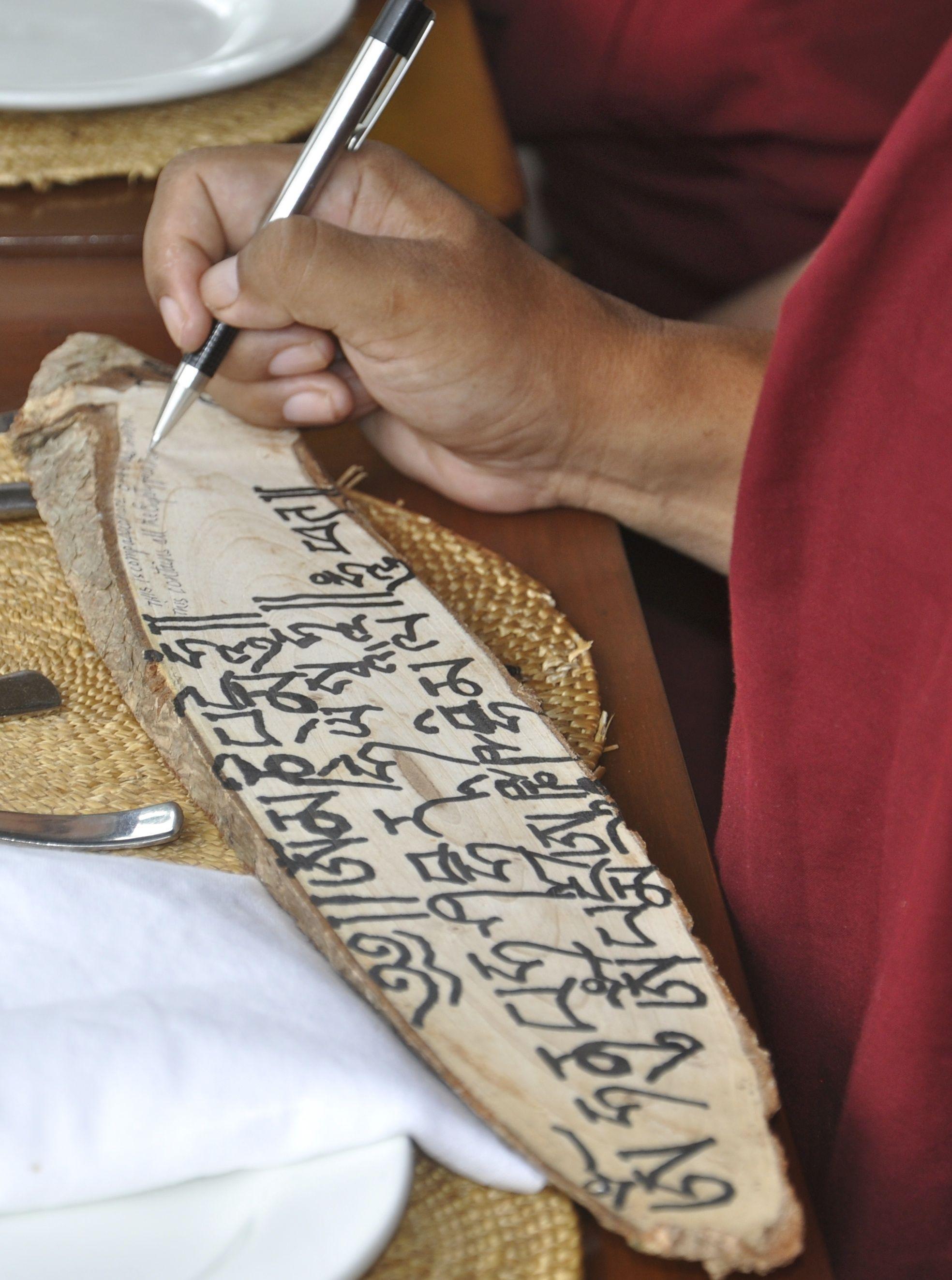 Rinpoche writesmantra on a souvenir plaque in Manali, India, 2015. (Photo Thubten Jangchub)